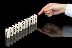 Hand Pushing Dominoes Counters On Black Stock Photos