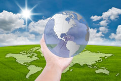 Hand pushing globe on the  blue sky field. Stock Photo