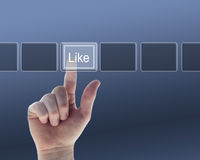 Hand pushing the like button Stock Photo