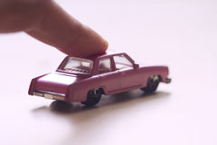 Hand pushing a pink toy car. Front view closeup of finger pushing forward a little miniature pink toy car on light background Stock Photos