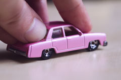 Hand pushing a pink toy car. Front view closeup of mature hand pushing a little miniature pink toy car on light background Stock Photos