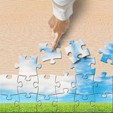 Hand pushing puzzles to assembly with beautiful landscape Royalty Free Stock Photos
