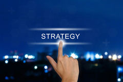 Hand pushing strategy button on touch screen Stock Photo