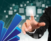 Hand pushing on a touch screen interface. Businessman hand pushing on a touch screen interface with blue  graph background Stock Images