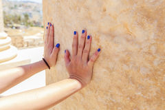 Hand pushing towards the granite wall at the ancient Roman city in Jerach, Jordan, summer time Stock Photo