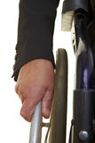 Hand pushing a wheelchair. Wrinkled old hand pushing an push rim wheelchair Royalty Free Stock Photo