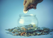 hand put coin  at  bottle of  money Royalty Free Stock Photos