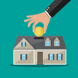 Hand put coin in piggy bank house Stock Images