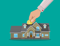 Hand put coin in piggy bank house Royalty Free Stock Photos