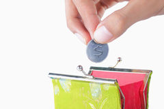 Hand put coin into the wallet Stock Photos