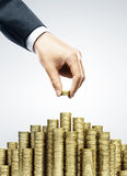 Hand put coins. To money staircase Royalty Free Stock Photo