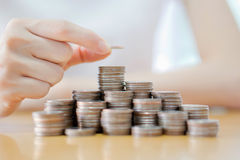 Hand put coins to stack of coins on white background. A Hand put coins to stack of coins on white background Royalty Free Stock Image