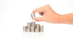 Hand put coins to stack of coins on white background Stock Images