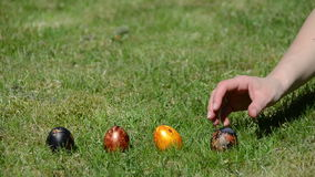 Hand put colorful painted eggs in a row and throw them to crash Royalty Free Stock Image