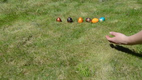 Hand put colorful painted eggs in a row and throw them to crash stock video