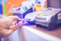 Hand put credit card In slot of credit card reader, credit card payment stock images