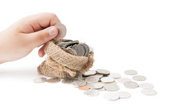 Hand put down money coin to sack isolated Stock Images