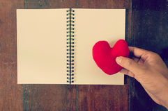 Hand put the heart on note book Stock Image