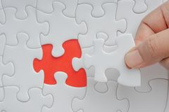 Hand put the last piece of jigsaw puzzle closeup to complete the mission. Selective focus and crop fragment royalty free stock photo