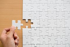 Hand put the last piece of jigsaw puzzle to complete the mission royalty free stock images