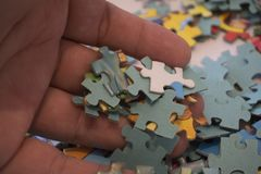 Hand put the last piece of jigsaw puzzle to complete the mission stock photo