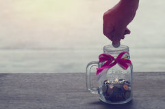 Hand put money coin on saving glas bottle Royalty Free Stock Image