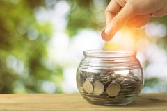 Hand put money coins on glass of jar on green bokeh background,. Hand put money coins on glass of jar on green bokeh background Stock Images
