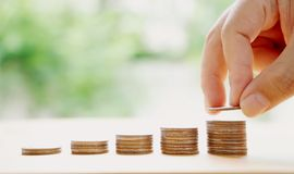 Hand put money coins to stack of coins. Money, Financial, Stock Photography