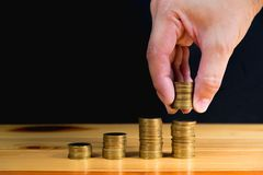 Hand put money gold coins to stack of coins on wooden table with. Black wall, Money, Financial, Business Growth and saving money concept, shallow focus. copy Stock Image