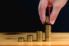 Hand put money gold coins to stack of coins on wooden table with. Black wall, Money, Financial, Business Growth and saving money concept, shallow focus. copy Stock Photography
