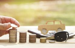 Hand put money on pile of coin with key of car, concept in finance Royalty Free Stock Image