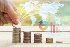 Hand put money on pile of coins concept in investment. With graph Royalty Free Stock Image
