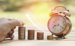 Hand put money on pile of coins. Concept in saving for growth in business Royalty Free Stock Images