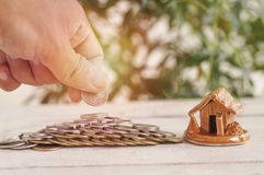 Hand put money on stacked. Of coins and house on wood background, concept in  growth, sell, buy, save and invest in business of home Stock Image