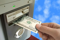 Hand put money to computer Stock Images
