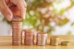 Hand put money to stack of coins Stock Photography
