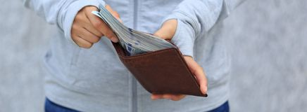 Hand put money into wallet. Female hand put money into wallet on blurred city background Stock Images