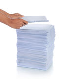 Hand put paper on stack of paper. Stock Photo