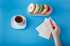 Hand put pen on painting heart with tea and donuts Royalty Free Stock Photos