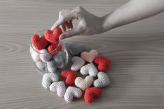 Hand put red Heart yarn in a glass jar, Vintage filter Royalty Free Stock Photo