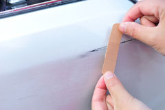 Hand put a sticking plaster at car scratches. Hand put a sticking plaster on car scratches Royalty Free Stock Image