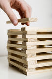 Hand puts block on tower Stock Photo
