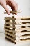 Hand puts block on tower Stock Photo