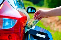 Hand puts the car into the gas tank one hundred dollars Stock Photo