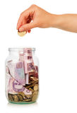 Hand puts coin in jar Royalty Free Stock Photos