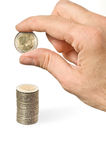 An hand puts a coin over a pile of money. White background Stock Image