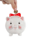 Hand puts a coin in a piggy bank Stock Images