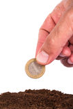 Hand Puts Coin into Soil Royalty Free Stock Photos