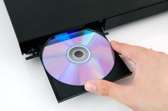 Hand puts the disc into the CD player Stock Photography