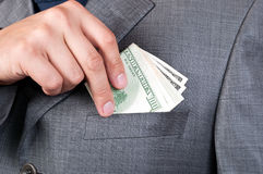 Hand puts dollars in the pocket Royalty Free Stock Photos